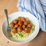 Zucchini noodles with meatballs and sauce on top in a bowl with fork