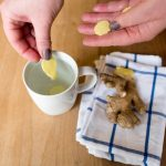 Hands holding and placing ginger into tea cup full of water